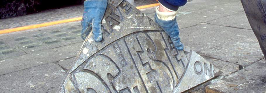 Metal casting being laid in pavement